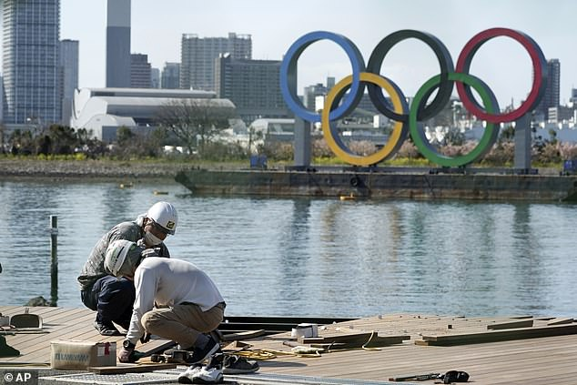 People work at a construction site with the Olympic rings in the background in Tokyo today
