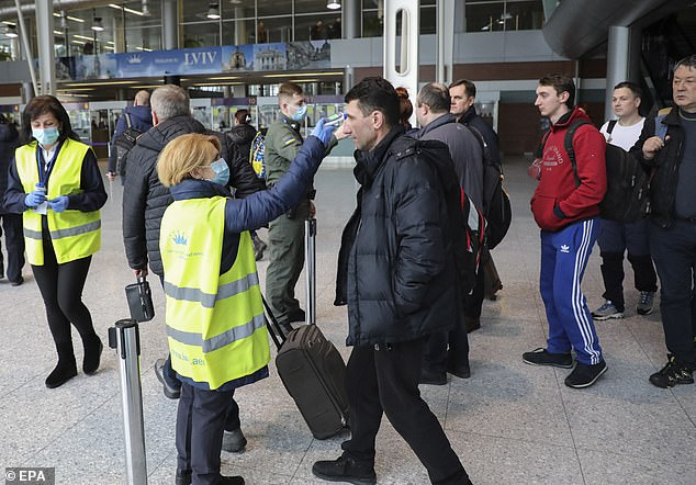 Health officials revealed a man tested positive after catching the deadly infection in Italy and travelling to Chernivtsi via Romania (airport workers at Danylo Halytskyi International Airport in Lviv, Ukraine, check the temperatures of travellers)