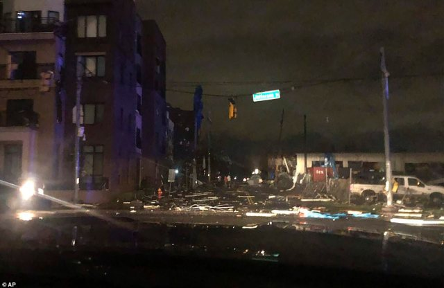 Debris scattered across an intersection (pictured above) in downtown Nashville this morning after the tornado hit the city