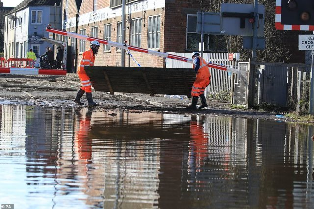 Workmen clear debris from the road where floodwater has begun to recede this morning in Snaith, East Yorkshire