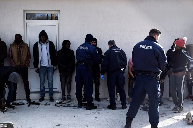Greek policemen check migrants at a border police station in the village of Neo Cheimonio after they crossed from Turkey