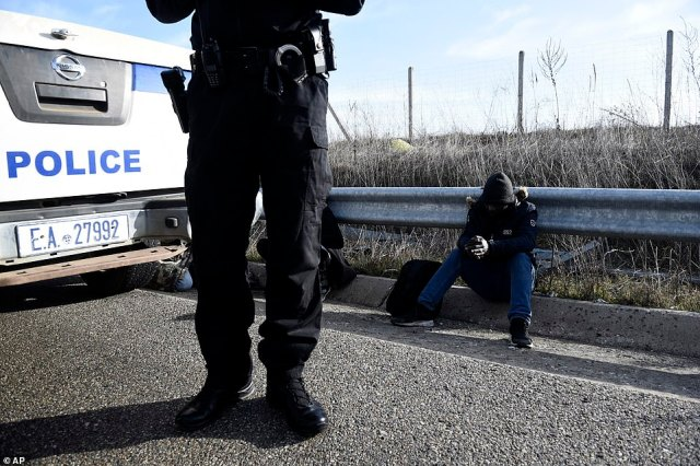 Migrants sit by the side of the road after being arrested by Greek police following a crossing from Turkey