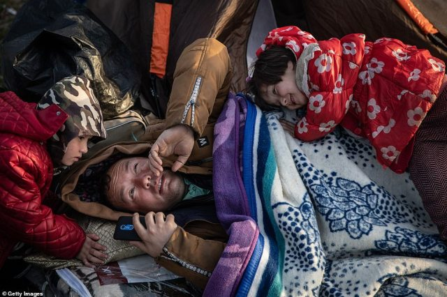 A man from Afghanistan rests as children play around him at a small refugee camp on the Turkish shoreline of the Evros River
