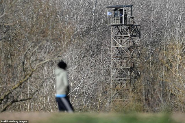 A migrant looks towards to Greek guard tower, near the Evros river, near Edirne, in northwestern Turkey, as he waits take a boat to attempt to enter Greece