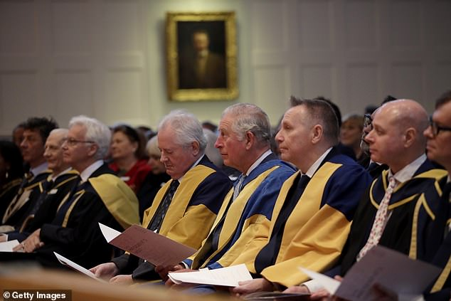 The royal listens to music being performed as he sits flanked by Director Professor Colin Lawson (C-L) and Chairman Lord Black of Brentwood (C-R) during the Royal College of Music's Annual Awards Ceremony at Royal College Of Music