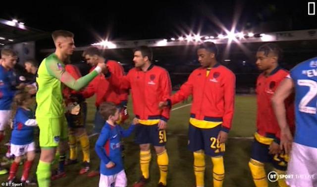 Arsenal defenderSokratis Papastathopoulos fist-bumps Portsmouth goalkeeper Alex Bass