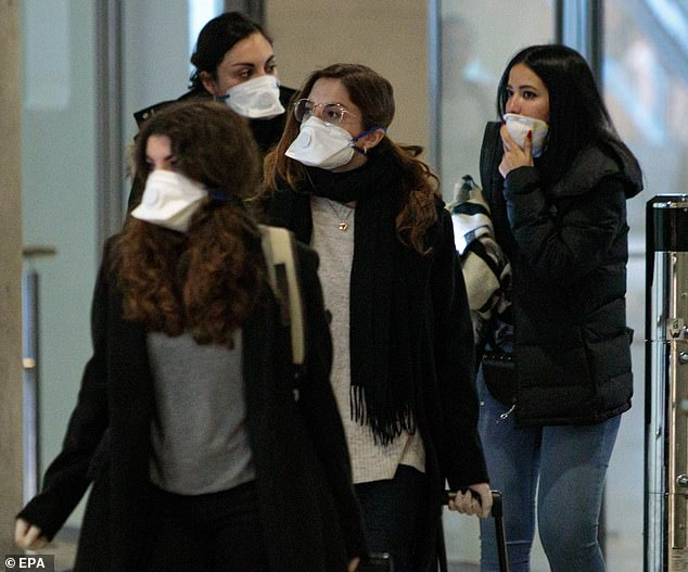 Travelers coming from Italy arrive at Valencia's Manises Airport while wearing facial masks, in Valencia, eastern Spain, 25 February 2020