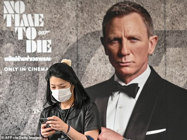 Crisis: The situation in China has already prompted the studios to push back release of the film in Hong Kong to April 30 and to cancel publicity tours in China, South Korea and Japan. (Pictured, a woman wearing a mask walks past a No Time To Die poster in Bangkok last week)