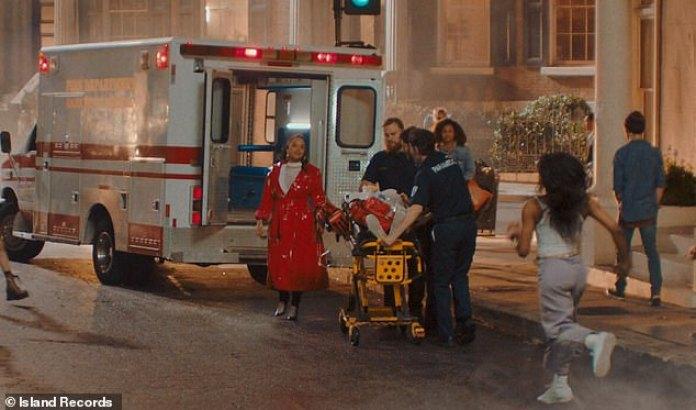 Sobrevivir y prosperar: después de un descanso de baile en la calle, toca el brazo de una mujer que rueda en una camilla en una ambulancia, simbolizando su sobredosis