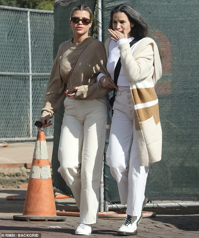 Twinning: Diane matched her daughter with a long cream and brown cardigan, a white sweater, white jeans and white combat boots