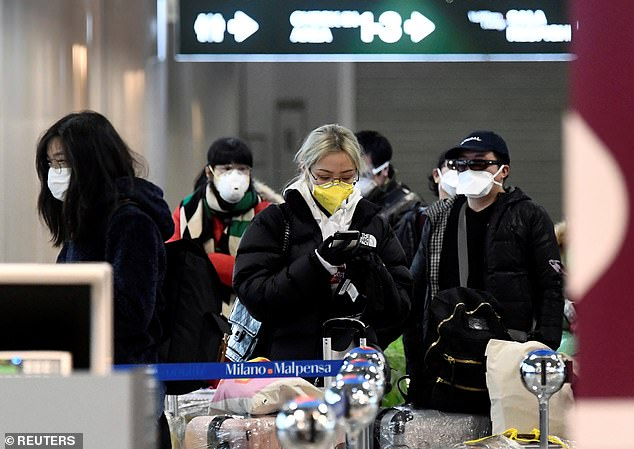 Passengers wearing protective face masks are seen inMalpensa airport near Milan, Italy.It is widely speculated that Italy has a stronger variant of the virus - known as the 'L' variant - but there is no concrete evidence for this