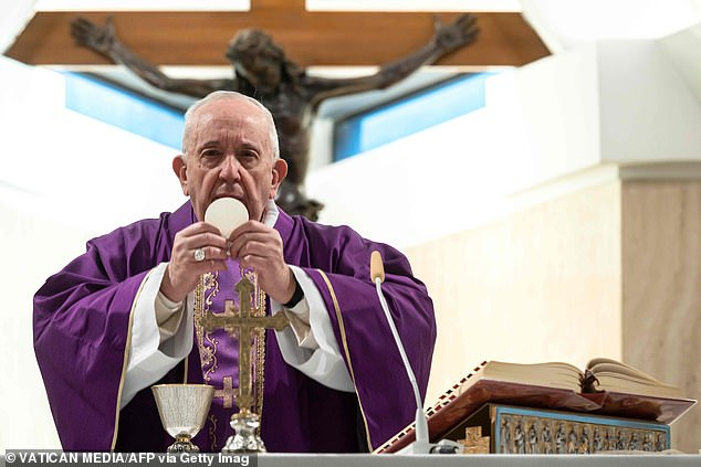 Francis lifts a communion wafer during his solitary mass in the Vatican this morning where he invited priests to visit coronavirus sufferers