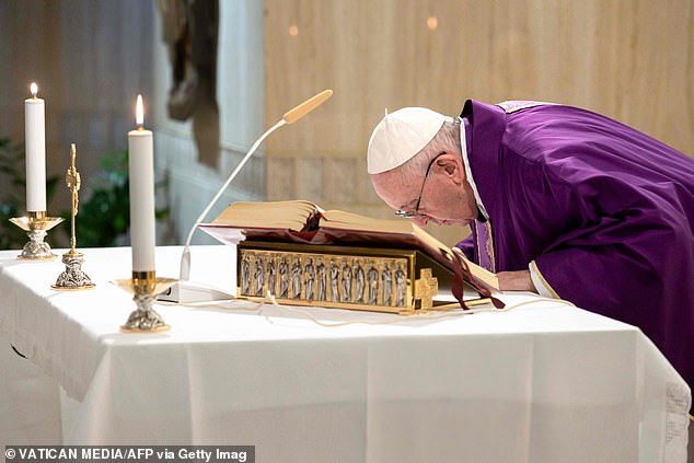 The pope leans towards the altar during today's mass in a chapel of the guesthouse of Santa Marta in the Vatican, where he lives