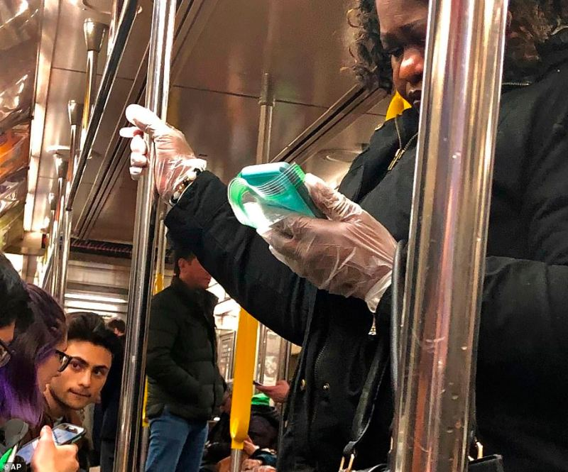 Commuters (pictured on a train in Manhattan on Monday) have been seen wearing protective gloves and adding extra casings to their phones during their New York City commutes