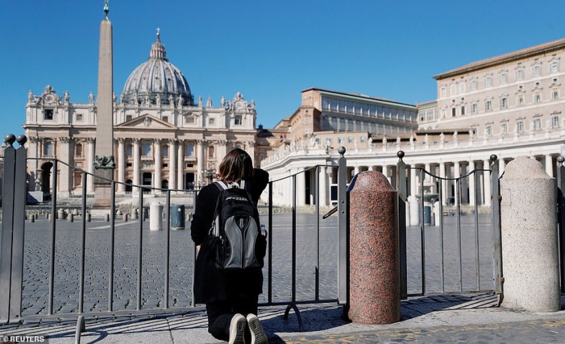 A woman looks towards St. Peter's Square and the Basilica behind it today after the usually popular tourist sites have been closed due to the coronavirus epidemic
