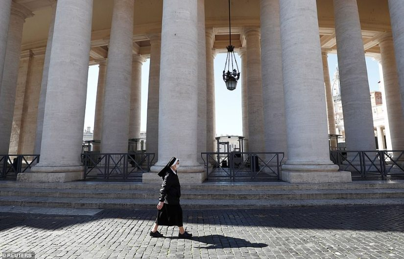 A nun wearing a protective mask today crosses Bernini's Colonnade which surrounds the closed Piazza San Pietro