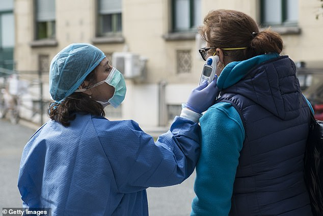 Medical staff checks the body temperature of a woman in front of the Molinette hospital in Turin as Italy clamps down on public events and travel to halt spread of the virus