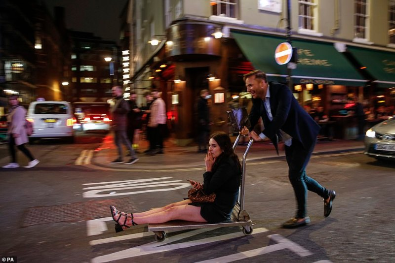 A man pushes a woman on a trolley through Soho, London, on unusually quiet streets. Defence sources told The Mail on Sunday that Army units were stepping up their training for public order roles