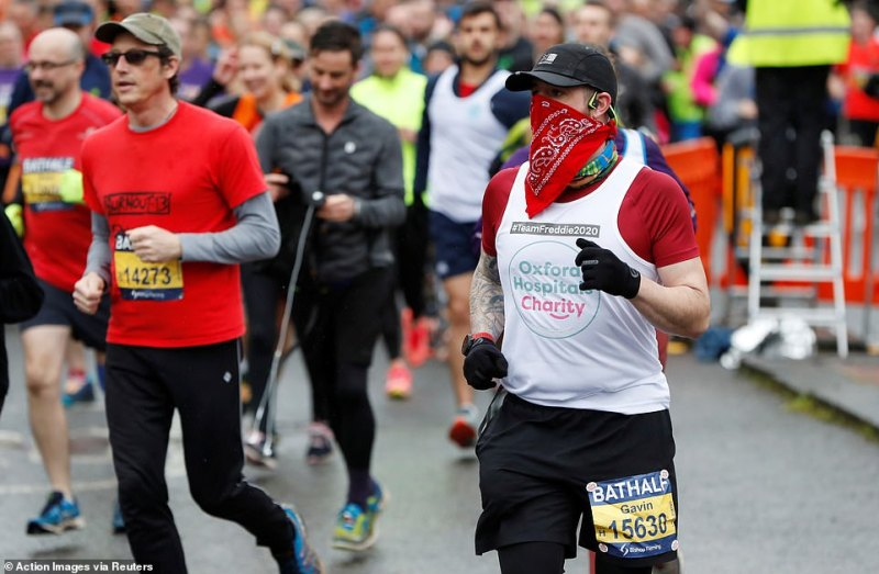 A runner wears a bandana over his mouth during the race as the marathon goes ahead despite MP Wera Hobhouse's warnings