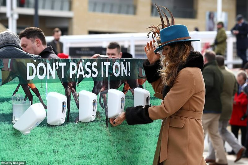 Race goers use hand sanitiser installed at Cheltenham Racecourse to help curb the spread of the Coronavirus