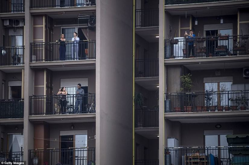 People were photographed standing on their balconies with pets and one with a dog in Rome yesterday