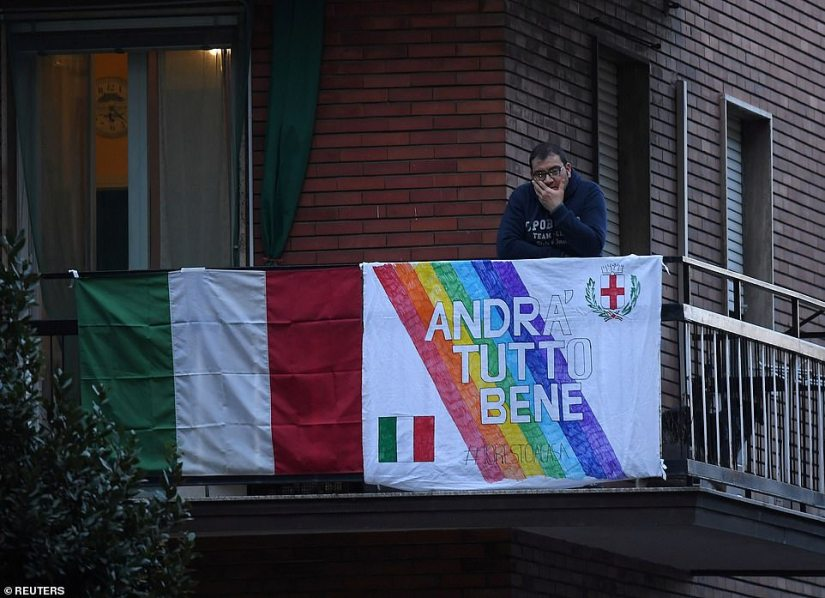 A man looks from the balcony of an apartment with a banner that reads