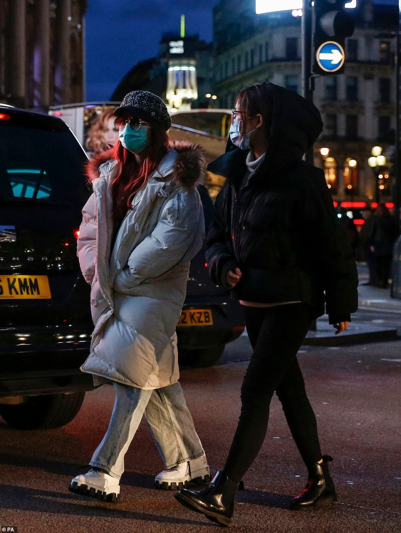 Two women cross the street wearing masks in Piccadilly Circus, London