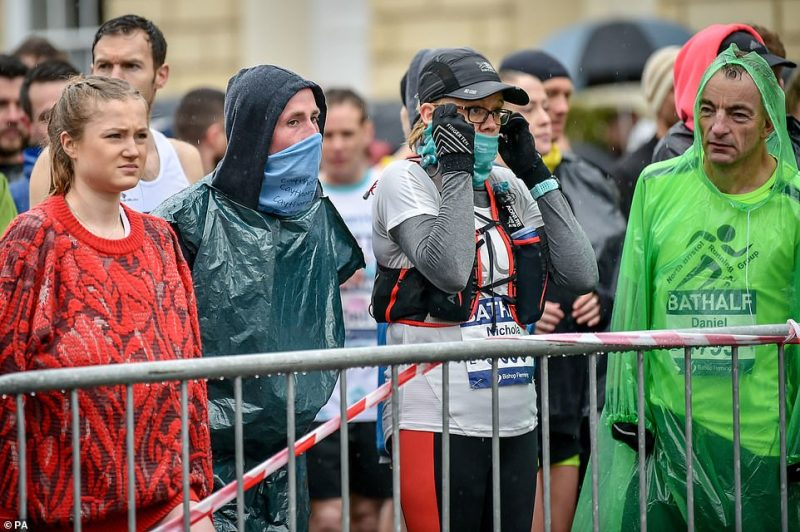 Runners wait at the starting line at the Bath Half Marathon, several covering their face in the rain