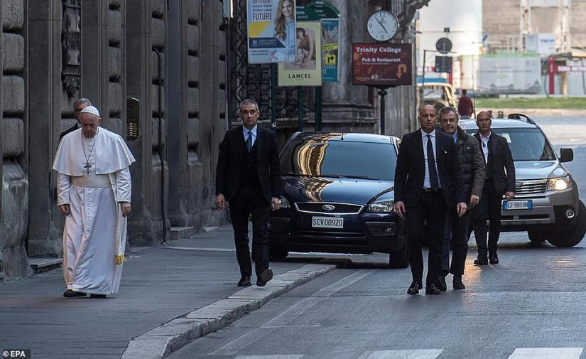 Flanked by his security details, Francesco walks along the usually animated Via del Corso in Rome