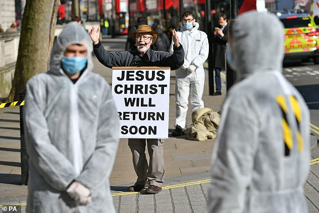 Prime Minister Boris Johnson is today facing mounting pressure for a dramatic escalation of the government's coronavirus response. Pictured, a religious street preacher alongside protesters wearing hazmat from a group called 'Pause the System' outside Downing Street