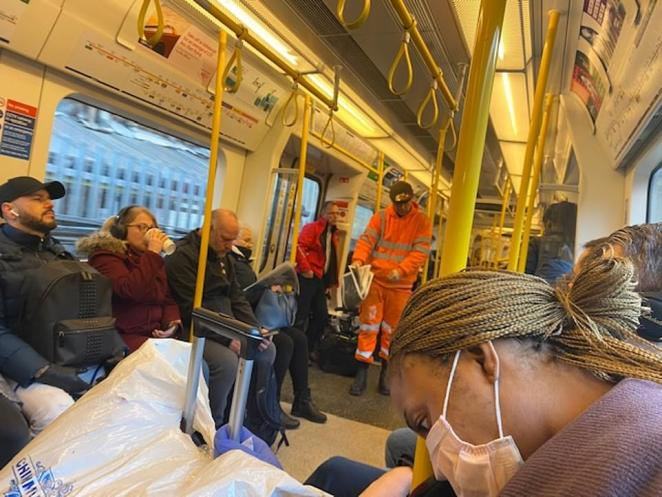 Commuters on a London train - one wearing a mask - go about their daily business this morning amid calls to stay at home