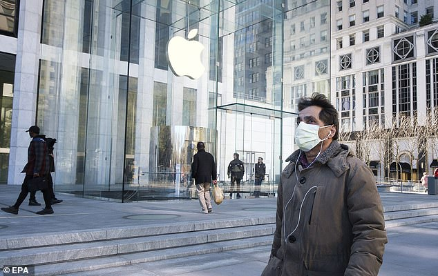 A man in a protective mask walks past a closed Apple Store on Fifth Avenue which is closed, along with most other Apple Stores around the world. However, this location is no shutdown until further notice