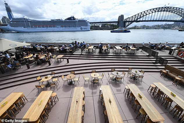 Empty tables are seen at bars outside the Sydney Opera House (pictured) on Tuesday, with such venues now likely to close entirely