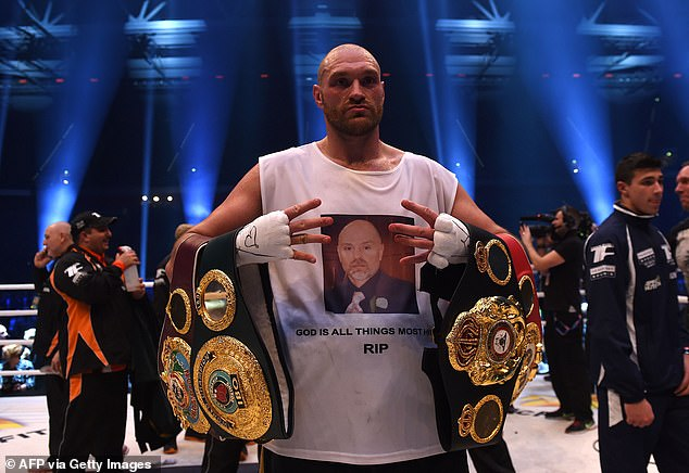 Fury celebrates with WBA, IBF, WBO and IBO titles after beating Klitschko in 2015