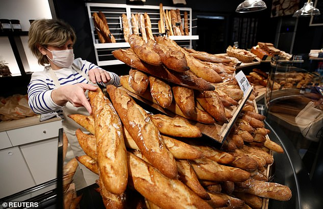 An employee, wearing a protective mask, exhibits some baguettes at the bakery 'Ma Boulangerie' in Vertou near Nantes while France is facing an aggressive progression of coronavirus disease (COVID-19), yesterday