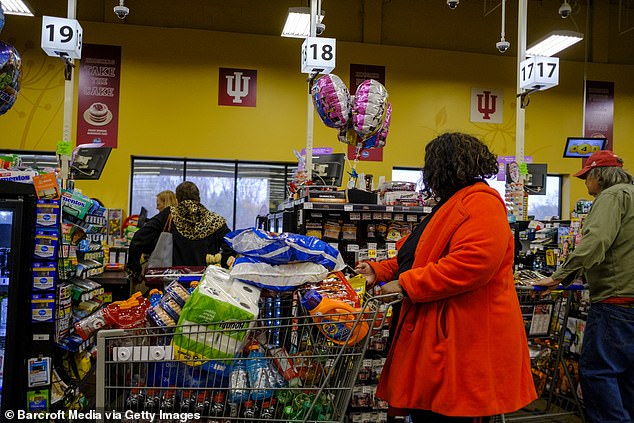 A woman waits in line to pay for a shopping basket full of food as shoppers fill a Kroger grocery store in Bloomington