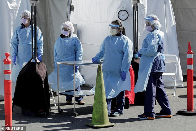 The authors of that study said slowing rates of infection in North American and Europe should occur between June and September. Pictured:Nurses wait for a patient in a car to pull forward to be tested for coronavirus in Seattle, Washington, March 18