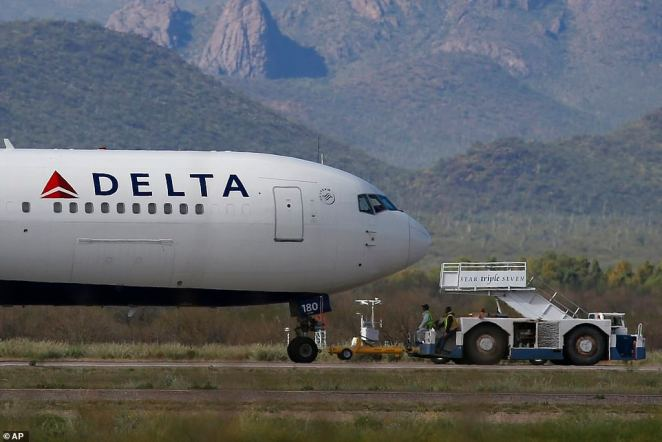 A recently landed Delta Air Lines airplane is worked on by ground crew at Pinal Airpark. This photo was taken in March