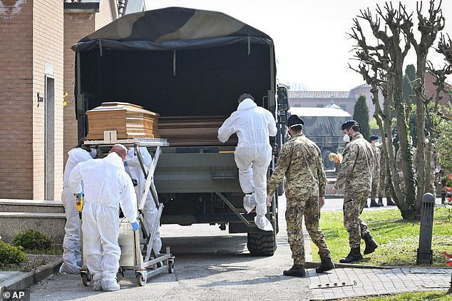 A convoy of Italian Army trucks is unloaded upon arrival from Bergamo carrying bodies of coronavirus victims to the cemetery of Ferrara, Italy, where they will be cremated