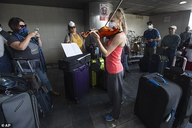 A traveller plays her violin prior to boarding a flight at La Aurora International Airport in Guatemala City