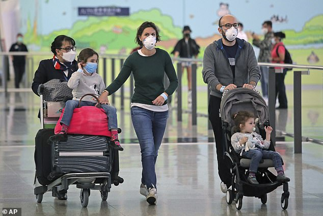 Passengers wears face masks after arriving at Hong Kong airport on March 23