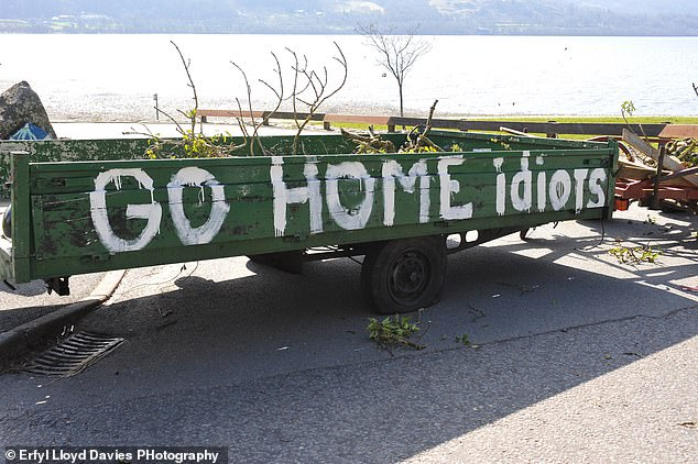 A landrover and trailer on the outskirts of Llyn Tegid at Bala Lake in North Wales telling visitors to go home