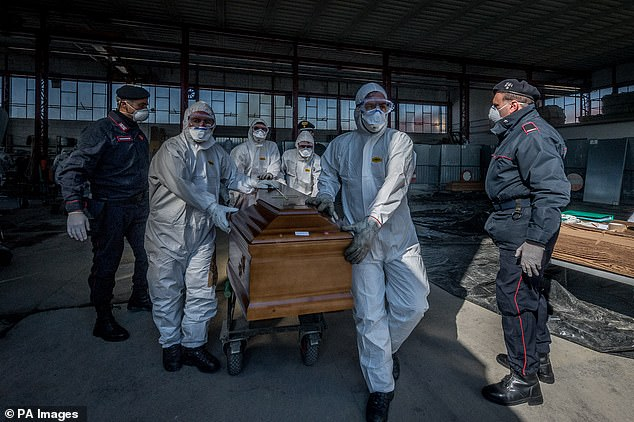Military and medical personnel wearing protective suits and masks for transportation transports coffins from a depot in Ponte San Pietro, near the hidden city of Bergamo in Italy