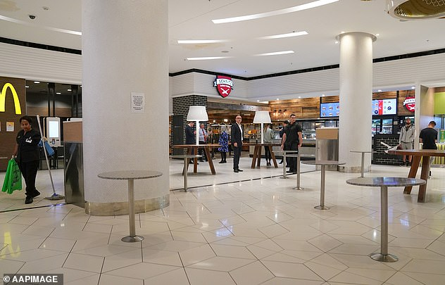 The governmentbanned people from eating in shopping centre food courts - with the exception of takeaway services' in new measures unveiled on Tuesday. Pictured: Chairs are removed from a food court in Melbourne to discourage eating in