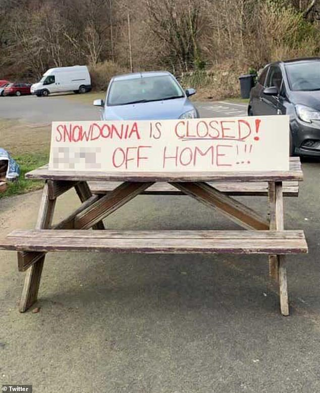 This angry sign in North Wales says: 'Snowdonia is closed. Go home! 'While locals launch themselves against tourists