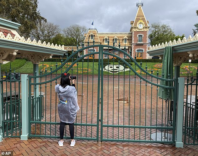A visitor to the Disneyland Resort takes a picture through a locked gate at the entrance to Disneyland on March 16. The closure of the park is having a dramatic effect on the company
