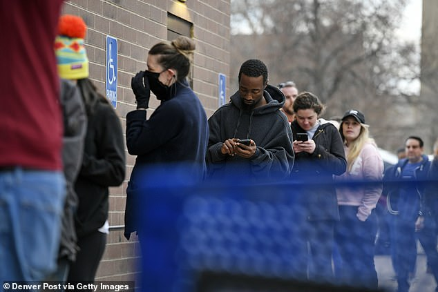 Some shoppers were seen wearing protective masks as they braved the outdoors to stock up on alcohol and marijuana before the shelter in place order in Denver took effect Tuesday. Shoppers waiting in a long line at Argonaut Liquors pictured Monday