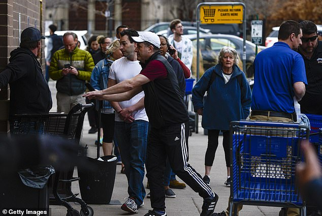 The city of Denver has amended a stay at home order to exclude liquor stores and marijuana dispensaries hours after long lines formed at the stores as locals attempted to stock up before the lockdown. Shoppers pictured in line at Argonaut Wine and Liquor on Monday