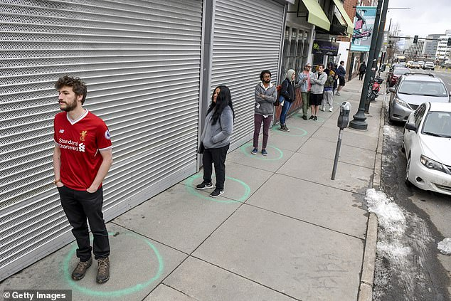 People stand in freshly painted circles, six feet apart, as they wait in a two-hour line to buy marijuana products from weed dispensary Good Chemistry on Monday in Denver