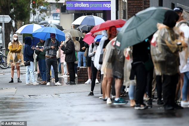 Not even the rain could reduce the crippling demand for assistance from Centrelink. Pictured is the queue outside Centrelink in Bondi Junction, in Sydney's east
